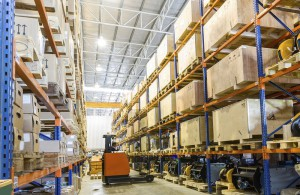 Modern fork lifter work in big warehouse